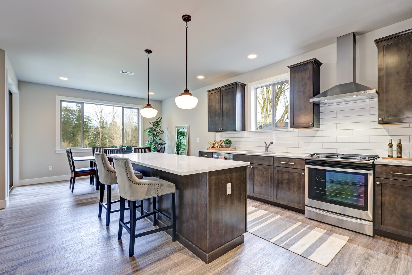 New kitchen boasts dark wood cabinets white backsplash subway tile and over sized island with white and grey quartz counter illuminated by pendant lights. Northwest USA