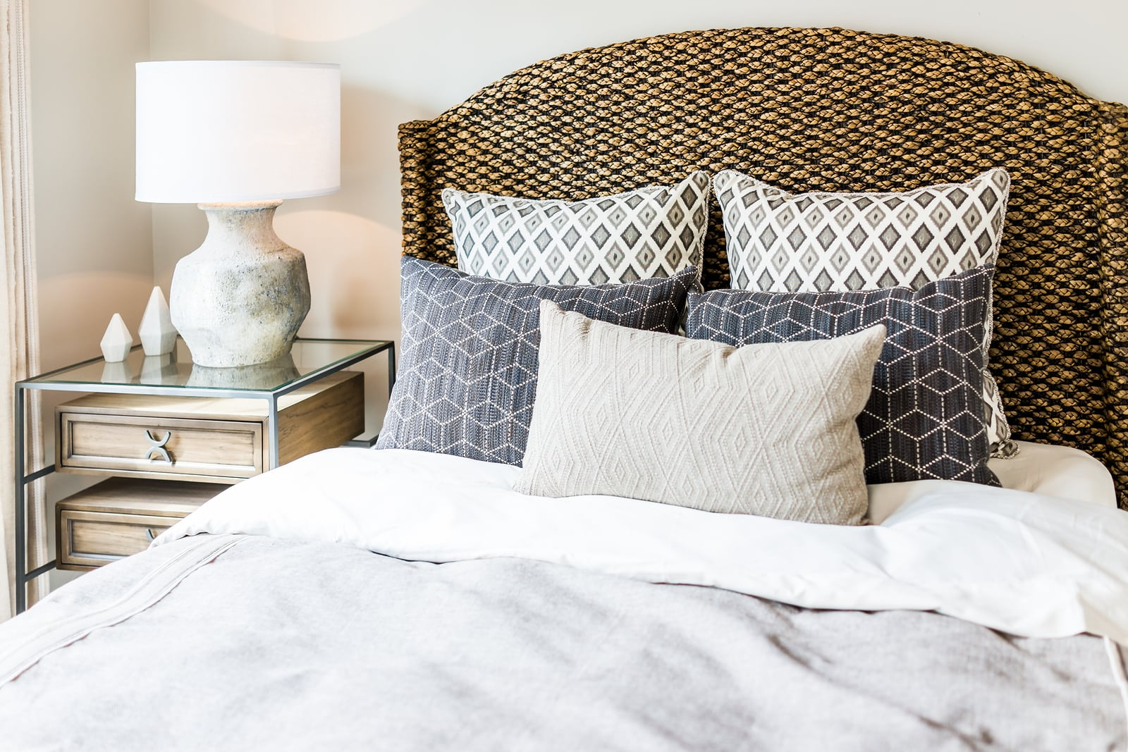 Closeup of new bed comforter with decorative pillows headboard in bedroom in staging model home house or apartment