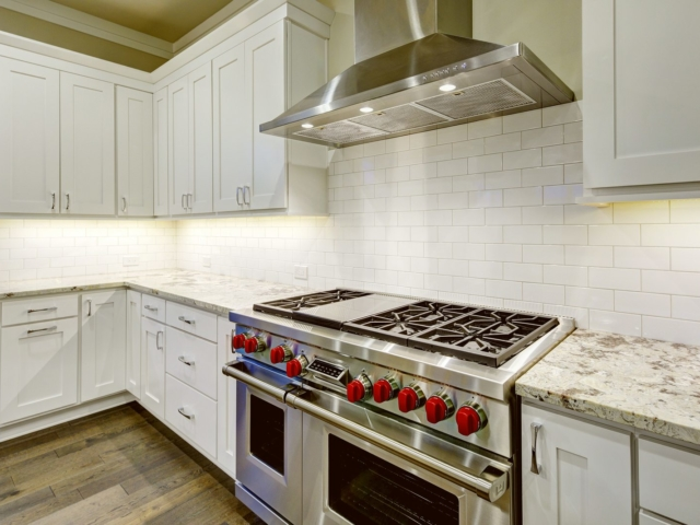 Large spacious kitchen design with white kitchen cabinets white kitchen island with lots of storage white Granite countertops subway tiles and stainless steel appliances. Northwest USA