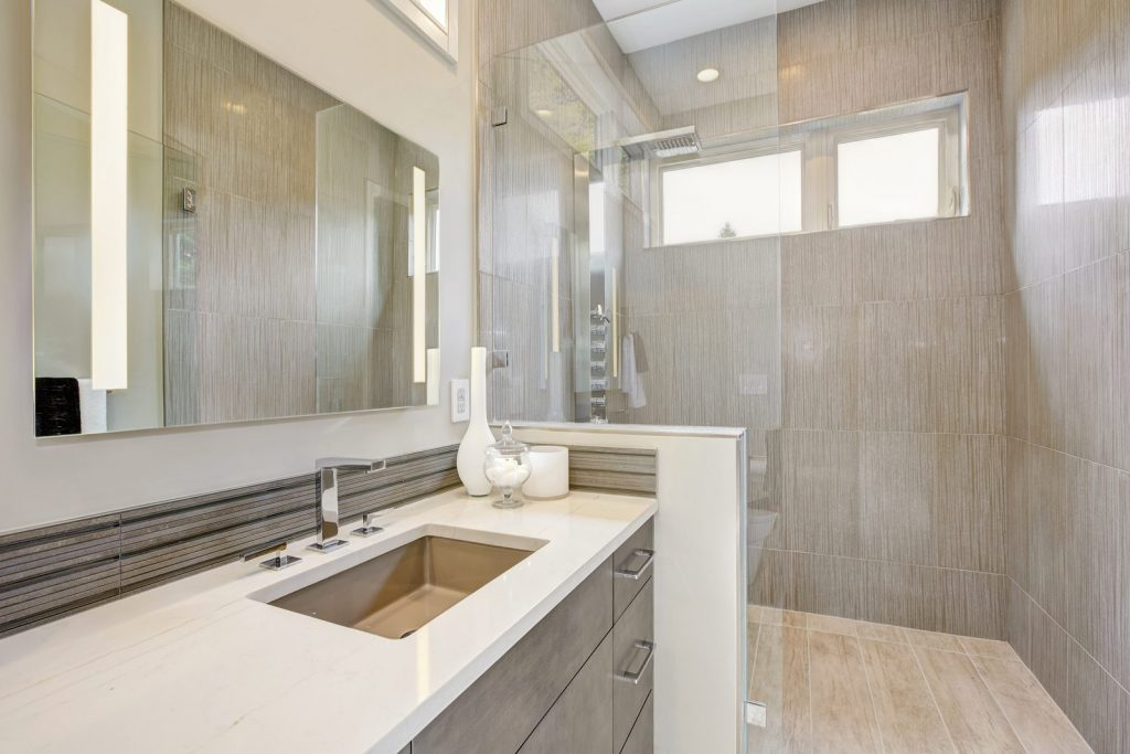 Contemporary bathroom features a dark vanity cabinet fitted with rectangular sink and walk-in shower. Northwest USA