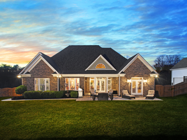 large brick house with stone patio, green grass and blue skies at dusk with the lights on