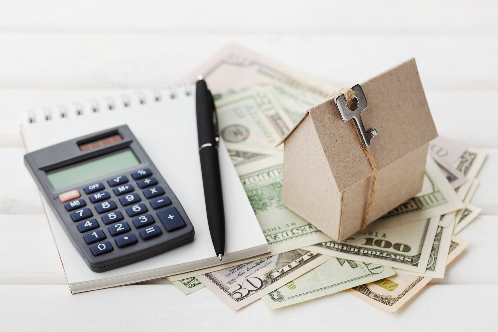 Model of cardboard house with key, calculator, notebook, pen and cash dollars. House building, loan and real estate. Cost of public utilities, insurance, rent or buying a new home concept.