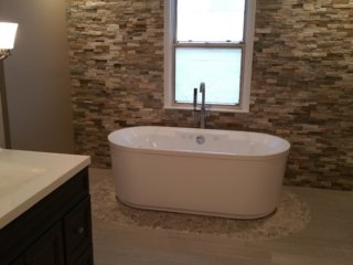 remodeled bathroom with tile floor, circular stone in lay and whirlpool