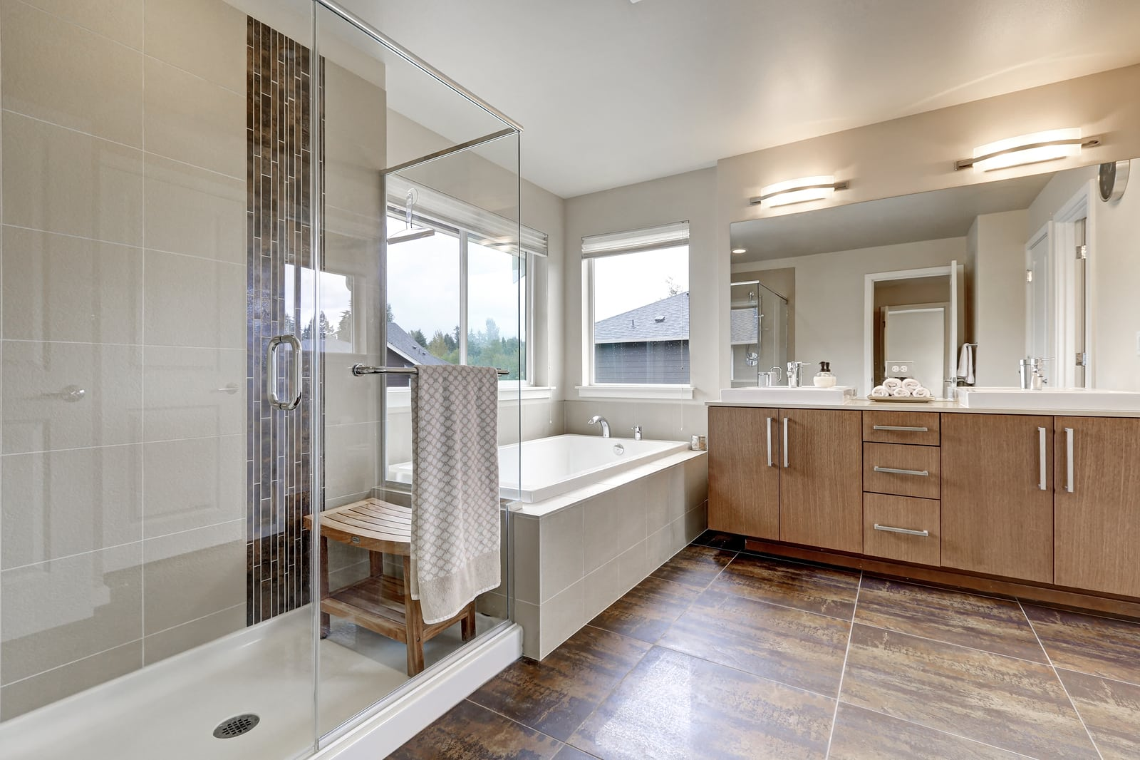 White modern bathroom interior in brand-new house. Double sink vanity with large mirror walk-in shower white bath tub and brown tile floor.