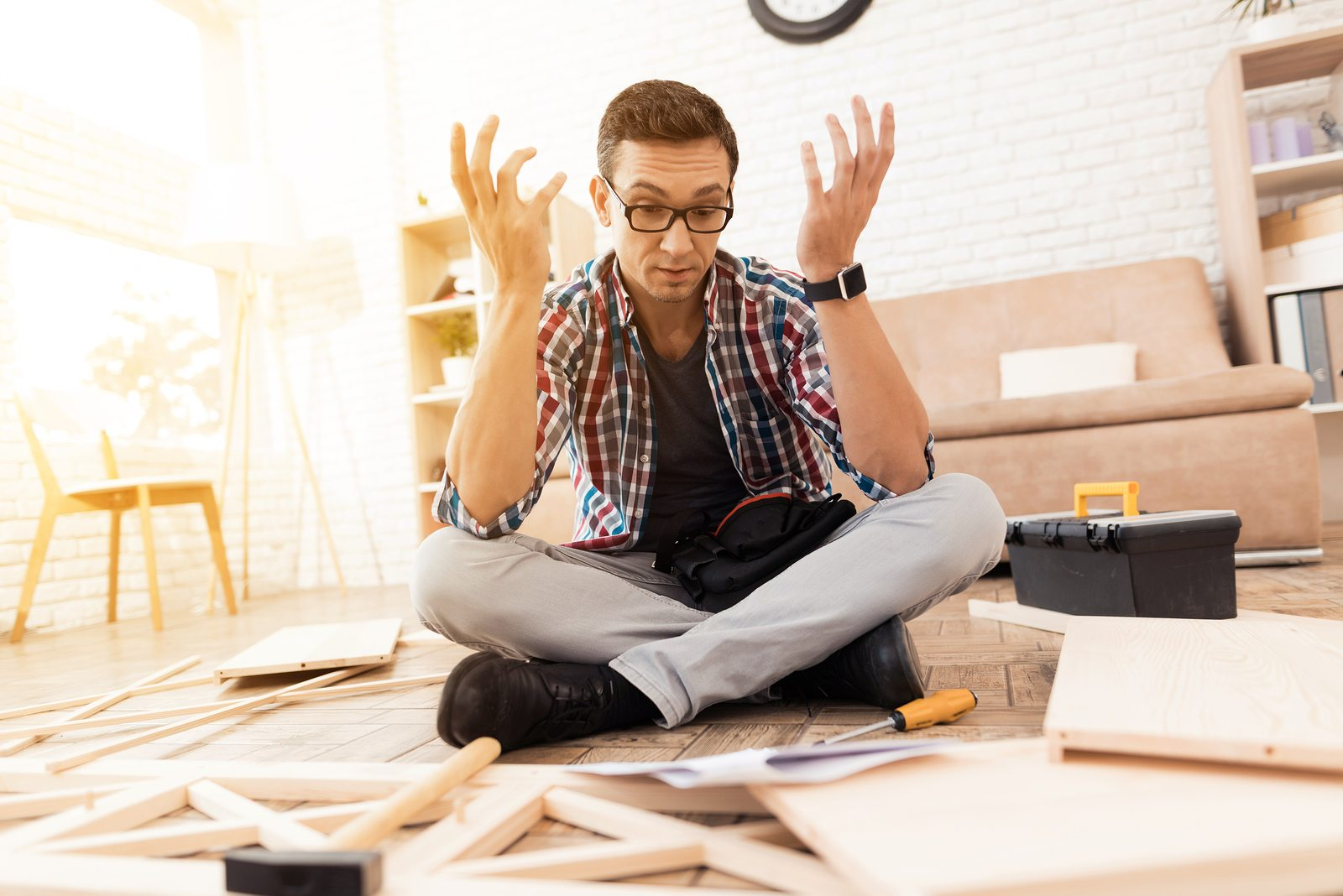 The young man tries himself to fold his bookcase. He reads the instructions. He uses tools for furniture. It turns out badly. He will use this furniture for the interior of his room.